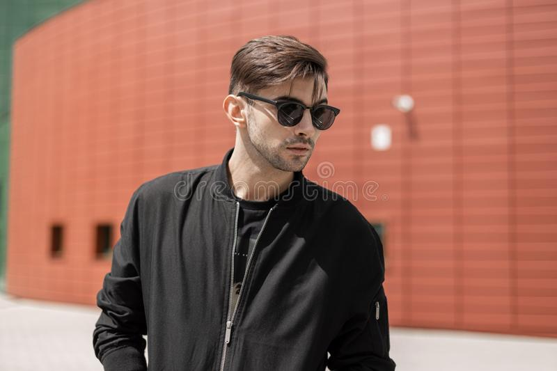 Attractive young hipster man in fashionable sunglasses in black trendy jacket with stylish hairstyle walks around the city. On a summer day. Handsome guy near royalty free stock photo