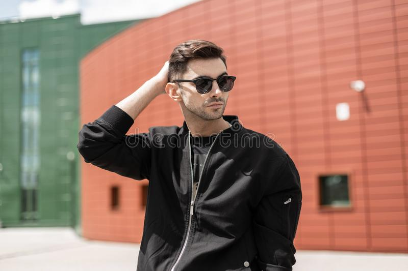 Attractive young hipster man in fashionable sunglasses in black trendy jacket with stylish hairstyle walks around the city. On a sunny summer day. Handsome guy royalty free stock images