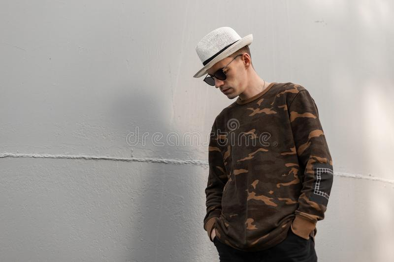 Attractive young hipster man in a vintage hat in stylish dark sunglasses in a fashionable camouflage shirt is standing stock images