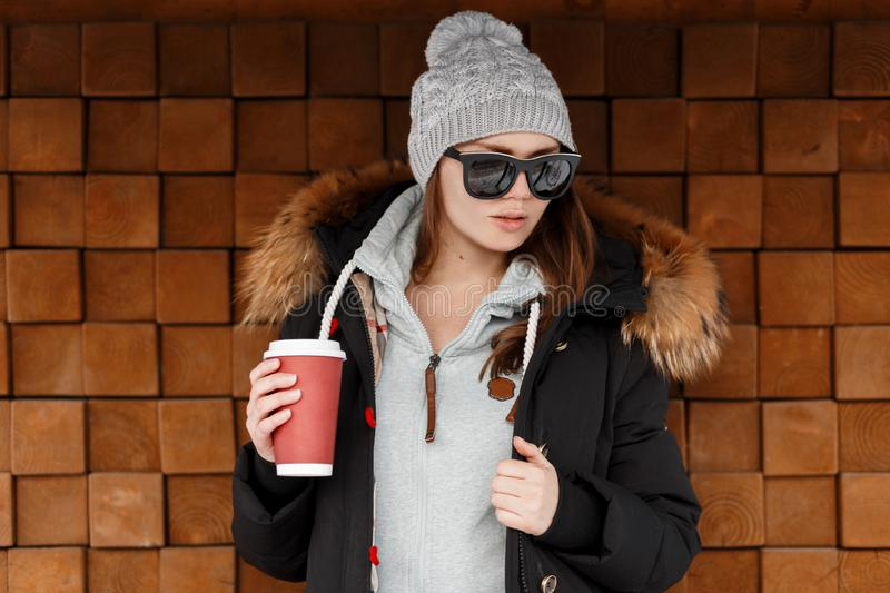Attractive young hipster woman in knitted hat in a sweatshirt in a stylish jacket in sunglasses posing near a wooden vintage wall. And holding a cup of coffee stock photography