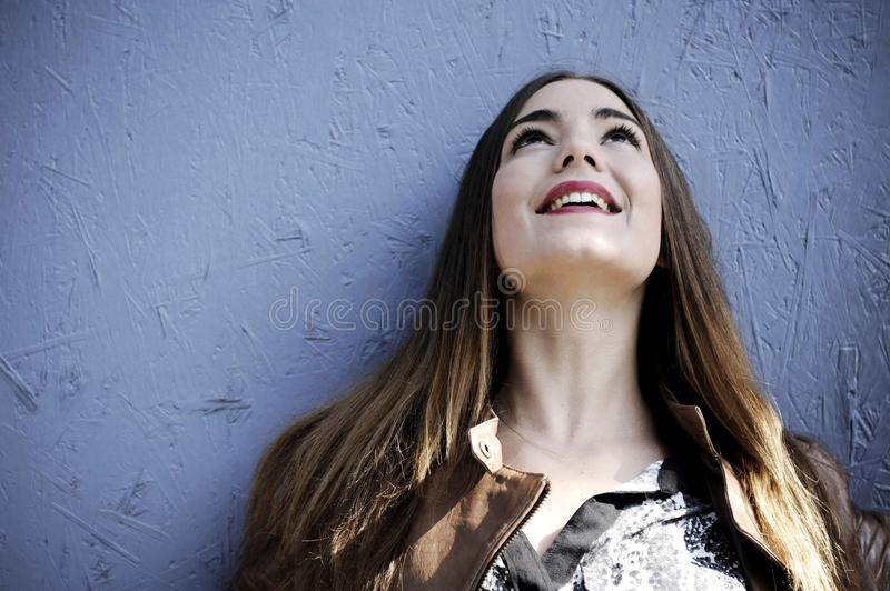 Attractive young hipster woman is standing against a blue wooden wall background with emotions on her face. royalty free stock photography
