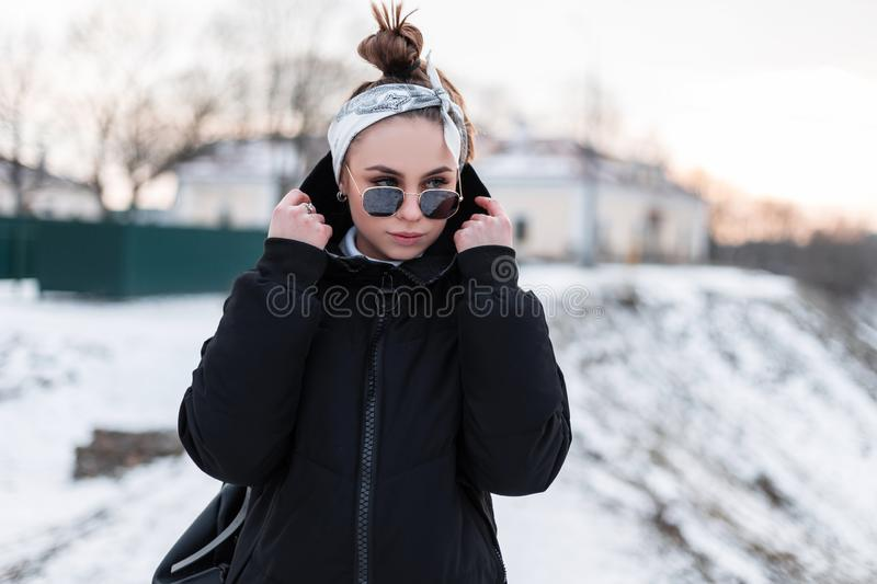 Attractive young hipster woman in stylish black sunglasses in black trendy winter jacket with a leather backpack with a bandana royalty free stock images