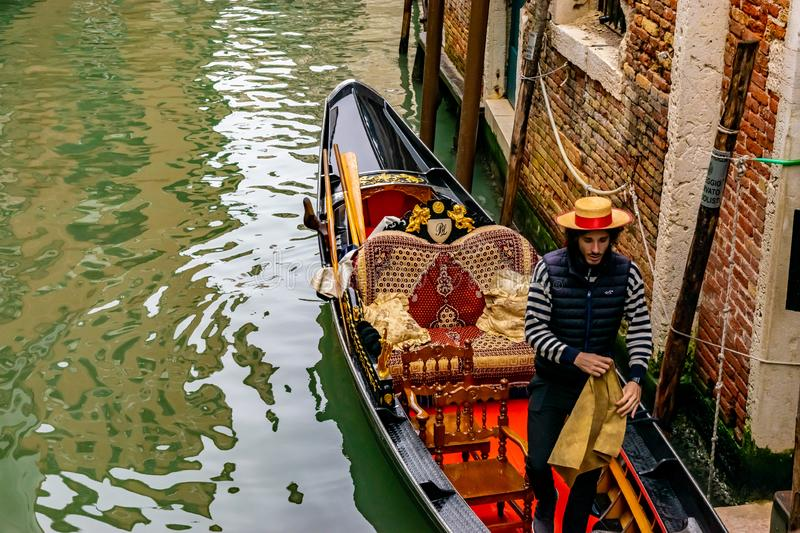 Attractive young Italian Gondolier wearing straw hat stands in traditional gondola with luxury decor stock photography