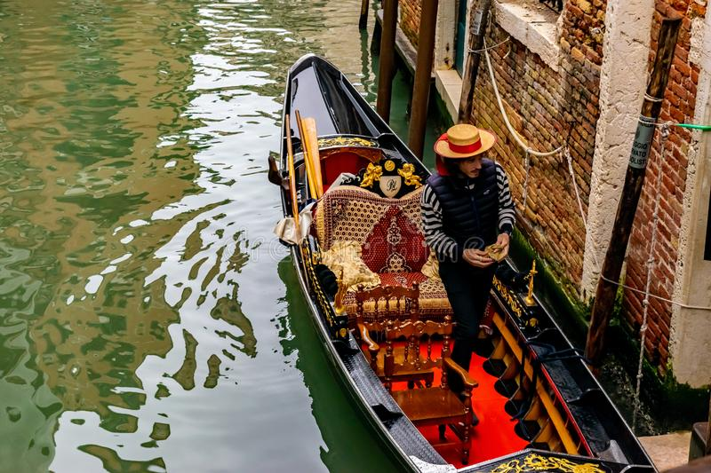 Attractive young Italian Gondolier wearing straw hat stands in traditional gondola with luxury decor royalty free stock photos