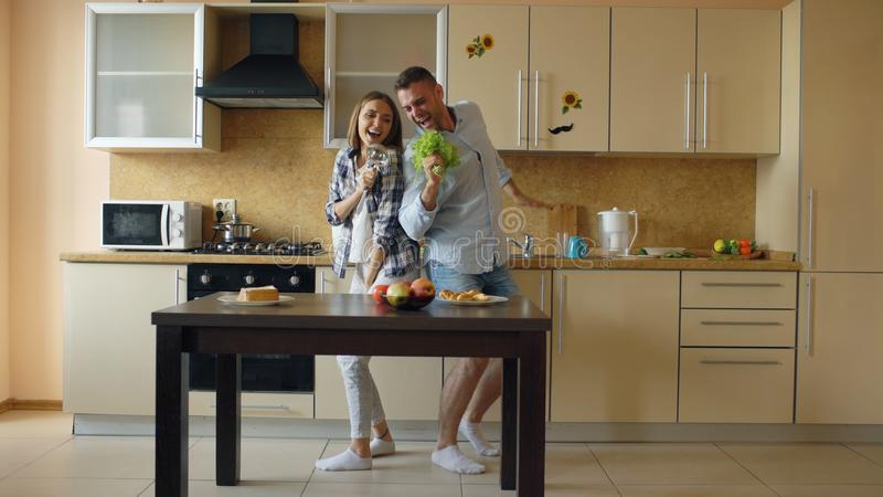Attractive young joyful couple have fun dancing and singing while cooking in the kitchen at home stock photography