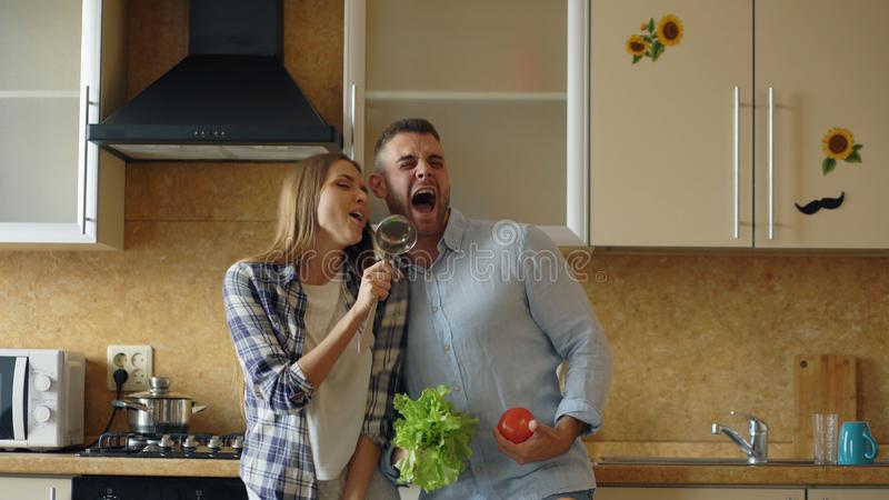 Attractive young joyful couple have fun dancing and singing while cooking in the kitchen at home. In the morining stock photography