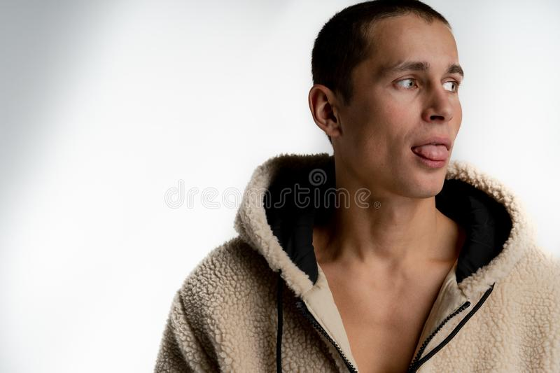 Attractive young joyful man with short haircut in white hoodie looking away showing tongue, isolated over white royalty free stock photos