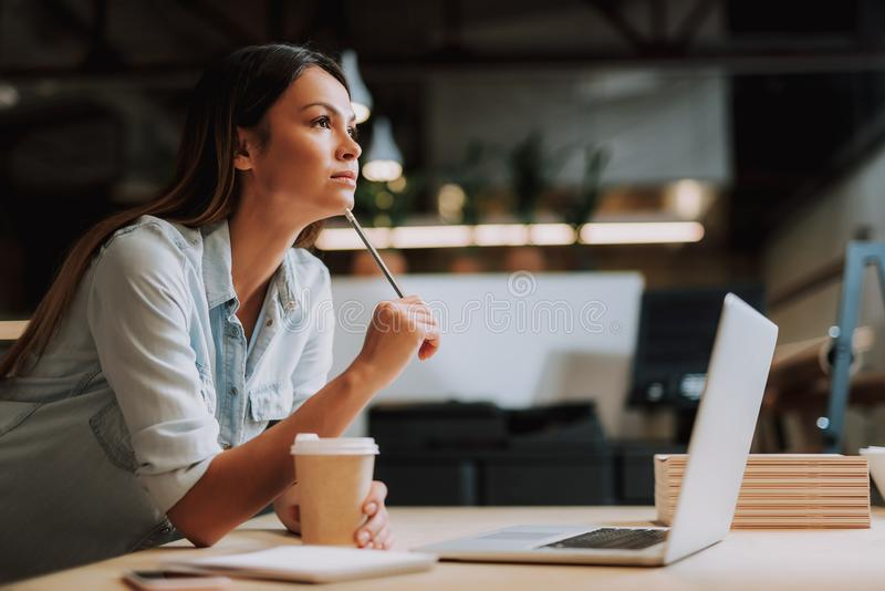 Attractive young lady with hot drink thinking about work project stock image