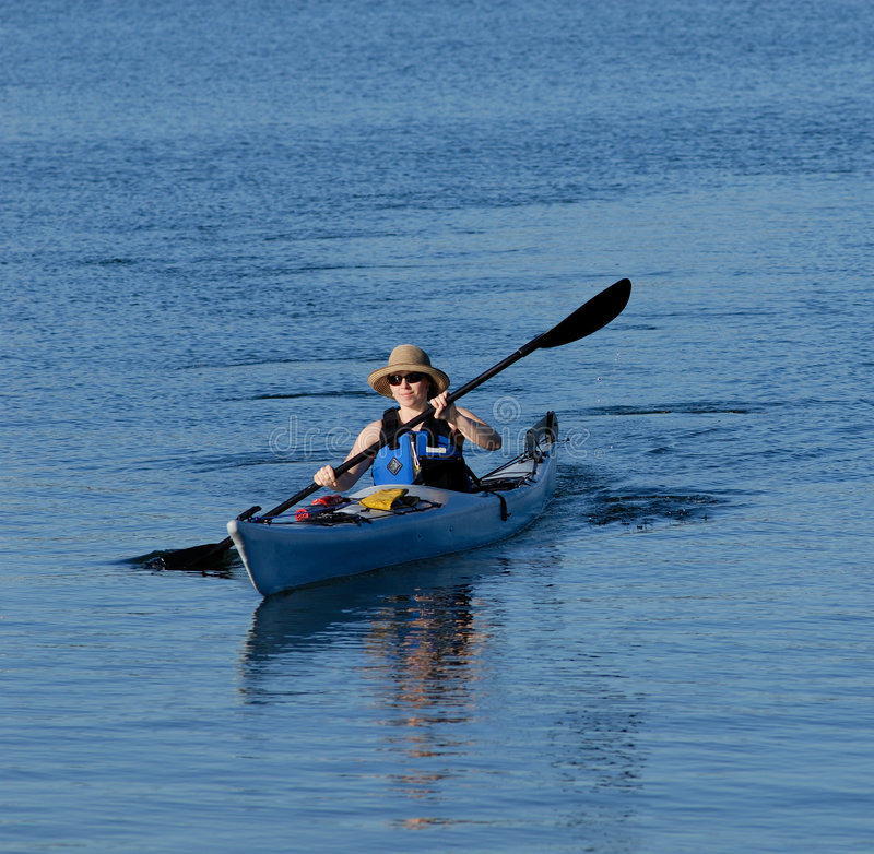 Attractive young lady kayaking. Attractive young female kayaker is rowing in deep blue sub-tropical waters of Mission Bay, San Diego, California royalty free stock images