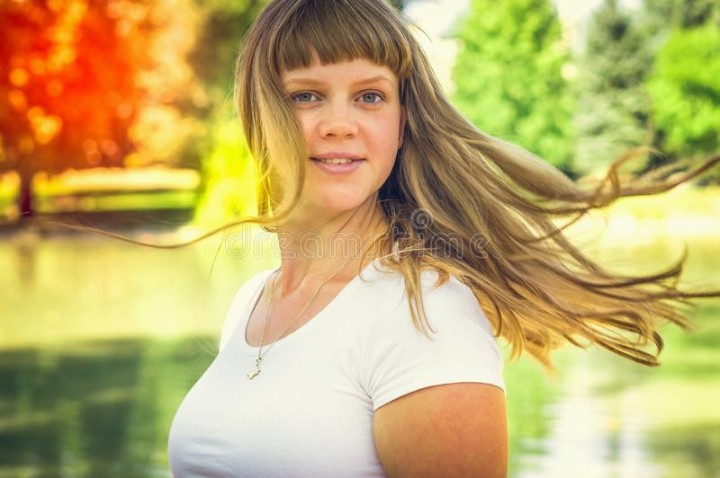 Attractive young lady in park enjoying in the nature royalty free stock image