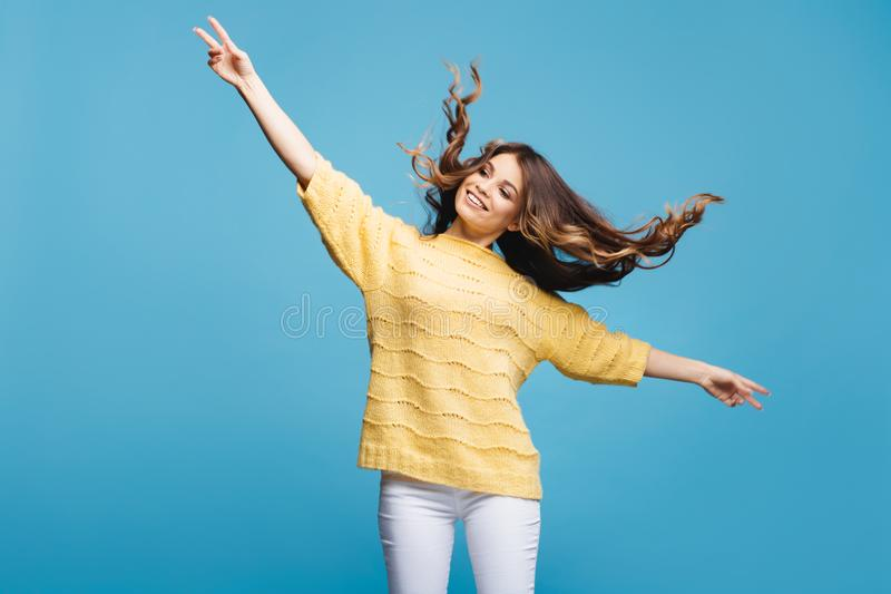 Attractive young lady posing on blue background. Pretty girl dance and having fun. Hair flying. royalty free stock photo
