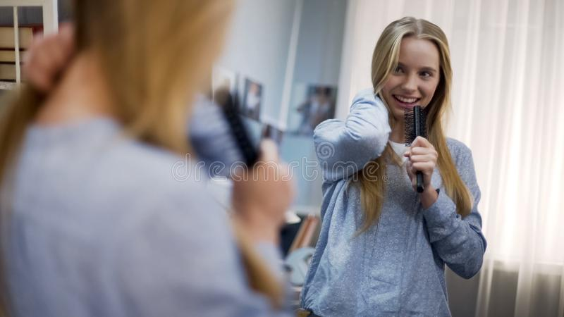 Attractive young lady singing to hairbrush as microphone dreaming of star career stock photo