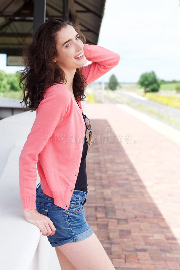 Attractive young lady smiling standing at train station waiting stock images