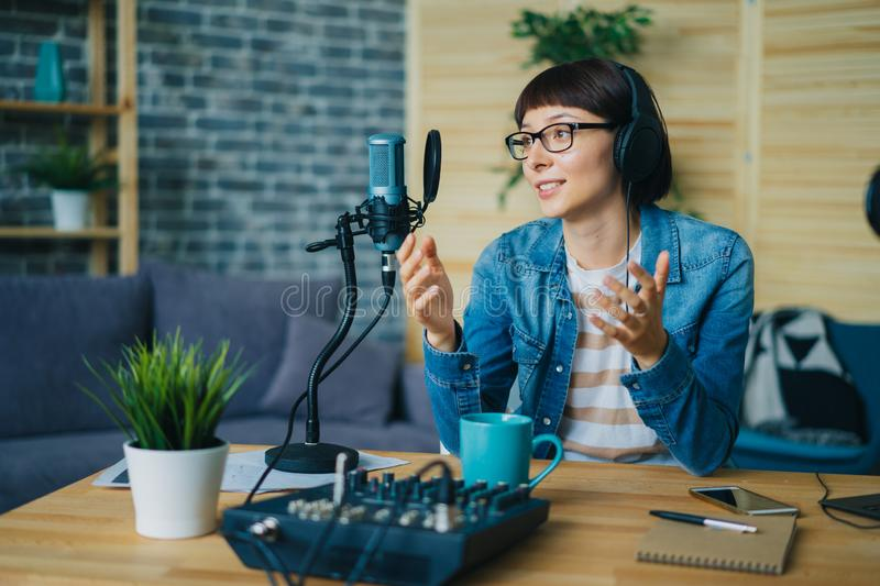 Attractive young lady speaking in microphone gesturing in studio. Attractive young lady blogger speaking in microphone gesturing sitting at table in studio using royalty free stock photo