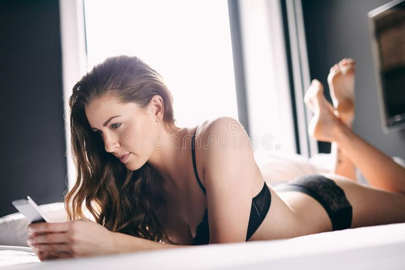Attractive Young Lady Using Cell Phone On Bed Stock Photo