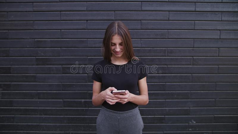 An attractive young lady wearing glasses using a phone against a brick wall background. Close-up shot royalty free stock photo