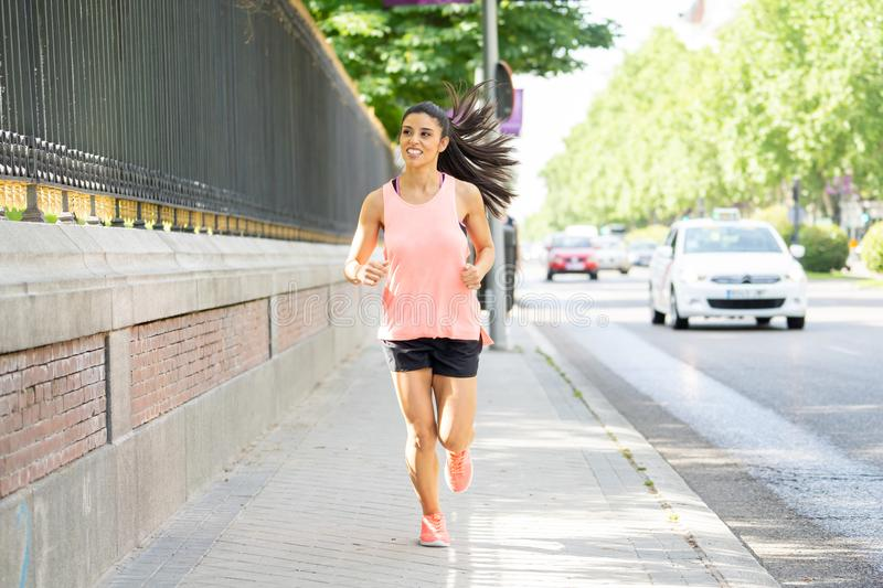 Attractive young latin female runner jogging in the city street in fitness concept stock photo
