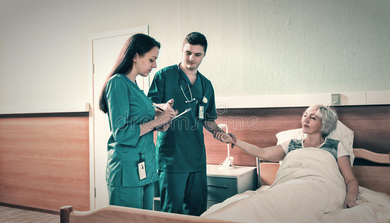 Attractive young male doctor and female nurse measuring the pulse and writing down complaints of patient royalty free stock photos