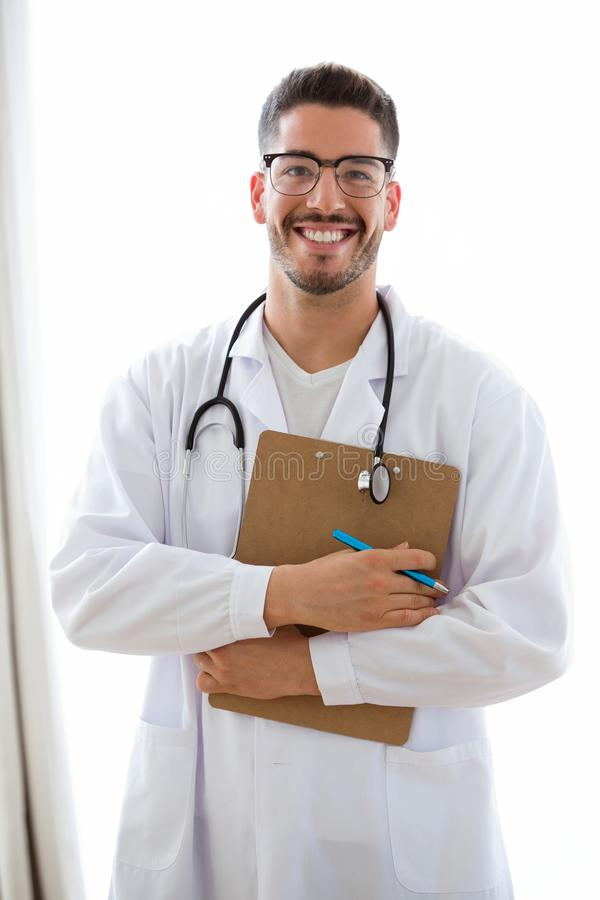 Attractive young male doctor with stethoscope over neck holding clipboard isolated on white. royalty free stock photography