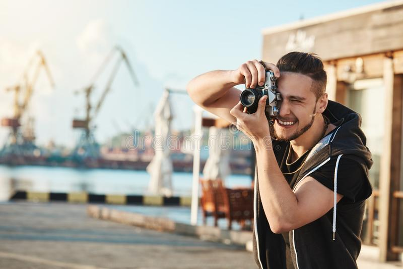 Attractive young male photographer walking along harbour, making photos of cool yachts and people, looking through royalty free stock photo