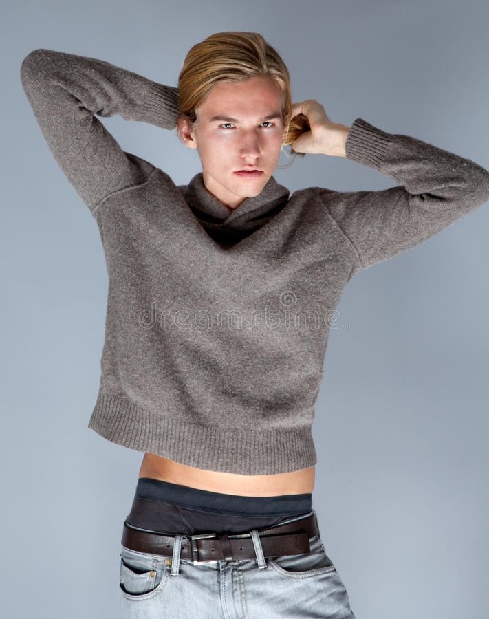 Attractive Young Man. A portrait of a gorgeous guy fixing his long hair and revealing a bit of belly royalty free stock photo