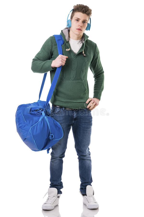 Attractive young man with bag on shoulder strap and headphones. Attractive trendy young man with bag on shoulder strap, listening to music with headphones royalty free stock images