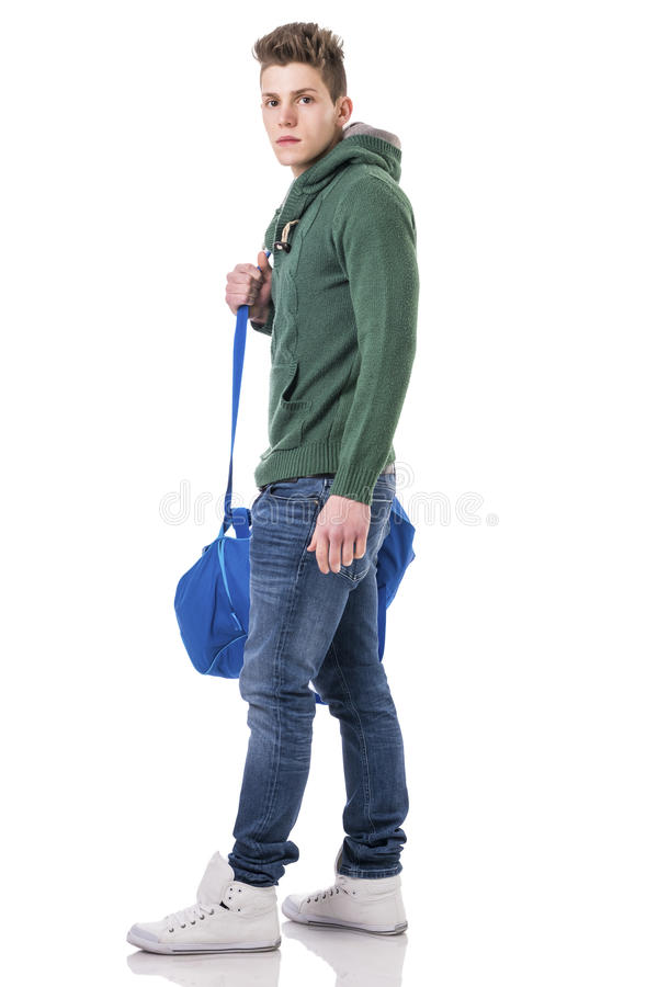 Attractive young man with bag on shoulder strap. Attractive trendy young man with bag on shoulder strap, isolated on white background, walking to left, looking stock images