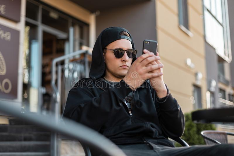Attractive young man blogger with a modern phone in a stylish hooded sweatshirt in vintage sunglasses in a cap sits royalty free stock image