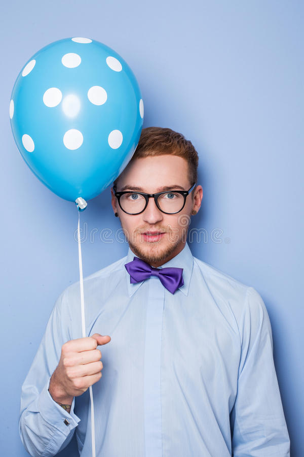 Attractive young man with a blue balloon in his hand. Party, birthday, Valentine. Studio portrait over blue background stock image