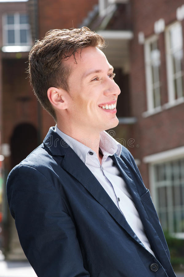 Attractive Young Man In Blue Jacket Smiling Outdoors Royalty Free Stock Image