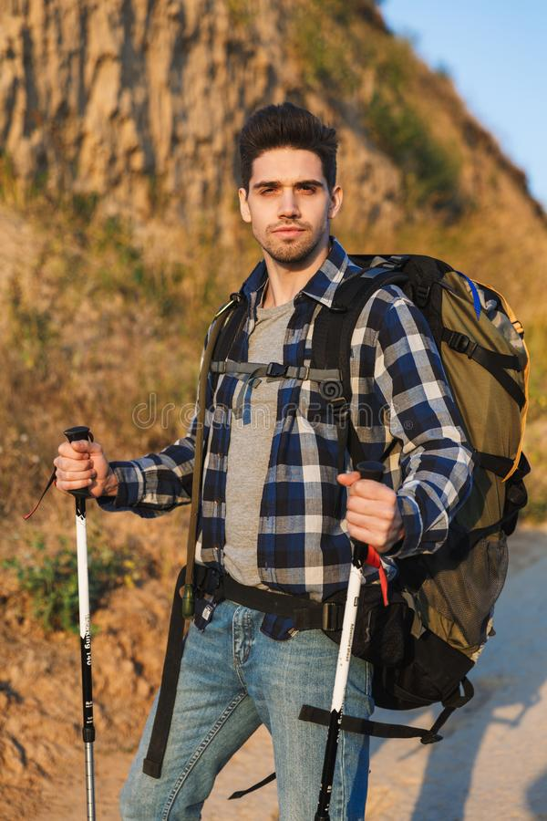 Attractive young man carrying backpack royalty free stock photography