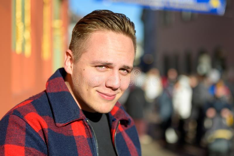 Attractive young man with a charismatic smile. Posing outdoors in sunshine in a colorful checkered jacket stock photo