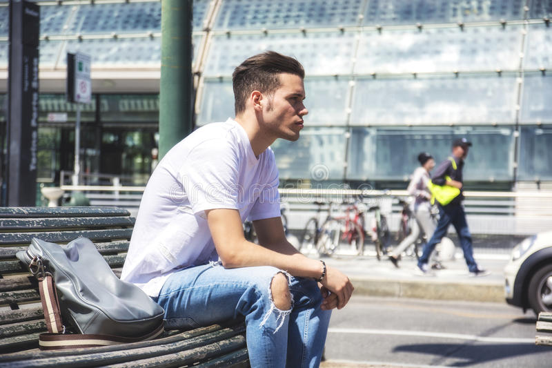 Attractive young man in city, sitting royalty free stock image