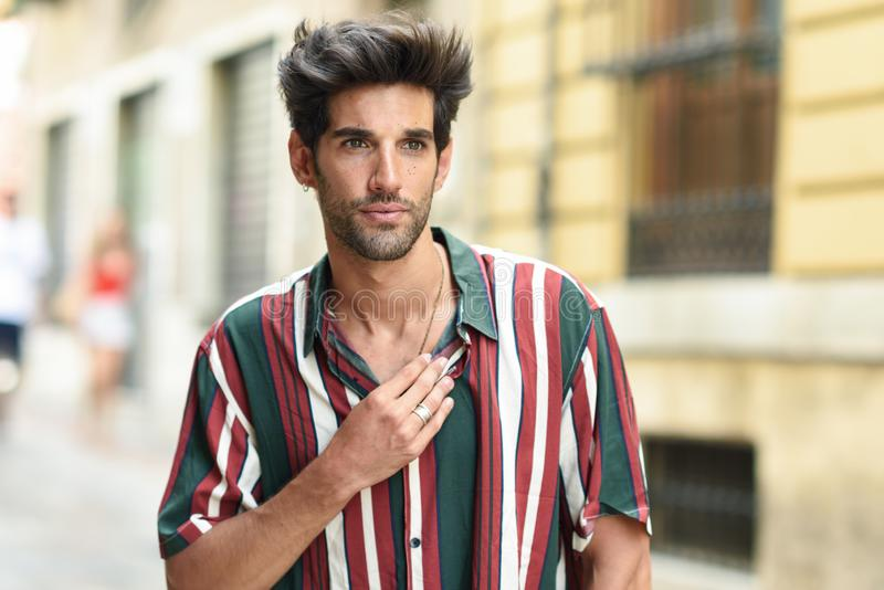 Attractive young man with dark hair and modern hairstyle wearing casual clothes outdoors royalty free stock photography