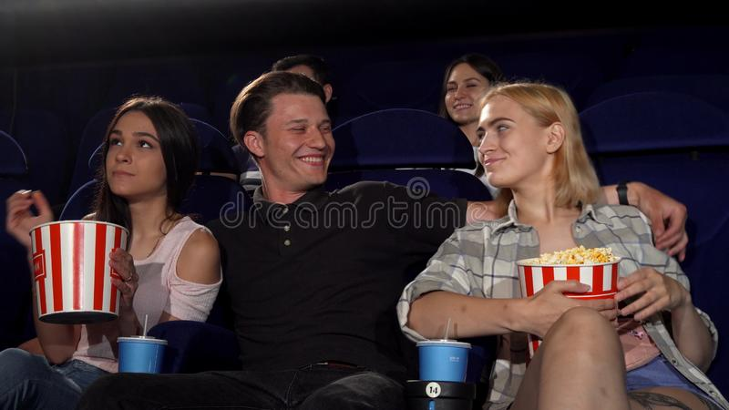Handsome young macho man hugging two girls at the cinema royalty free stock images