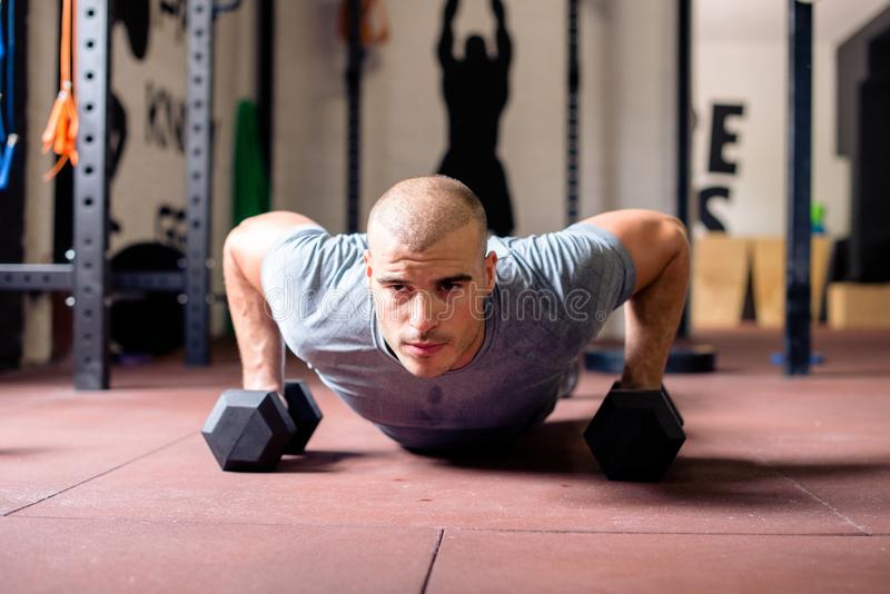 Attractive young man doing push-ups with weights. In gym stock photo