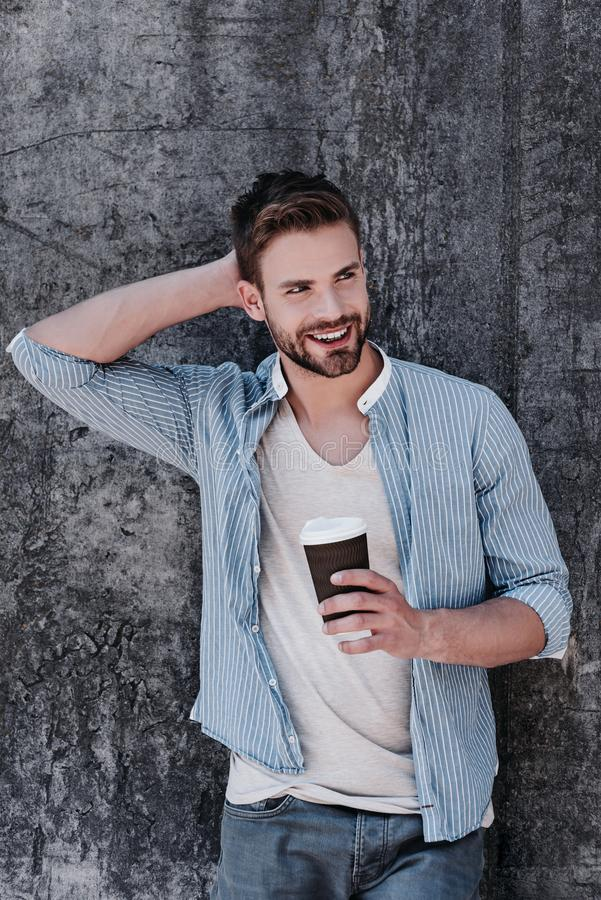 To help have less stress, take time to relax. brown-haired man with blue eyes standing isolated over grey stock photo