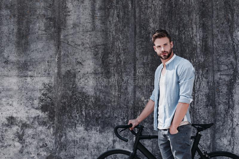 Nothing compares to the simple pleasure of riding a bike. Handsome brown-haired man with blue eyes standing with a royalty free stock photos