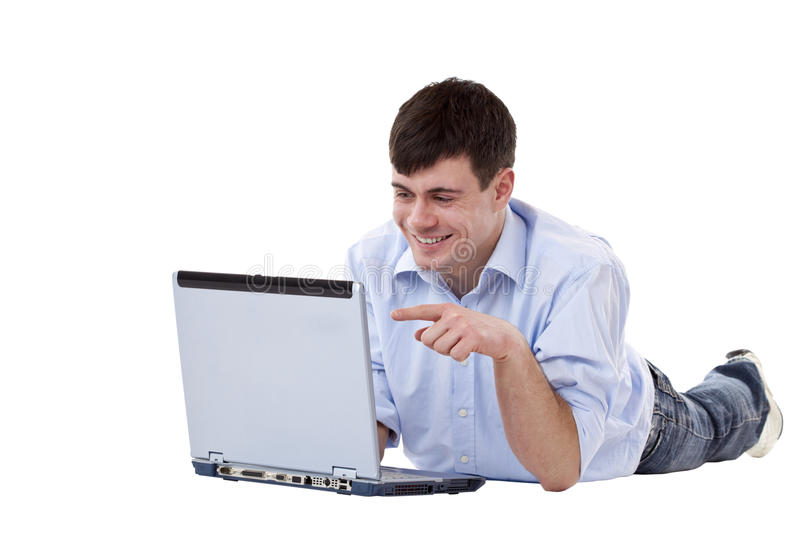 Attractive young man on floor pointing at computer royalty free stock image