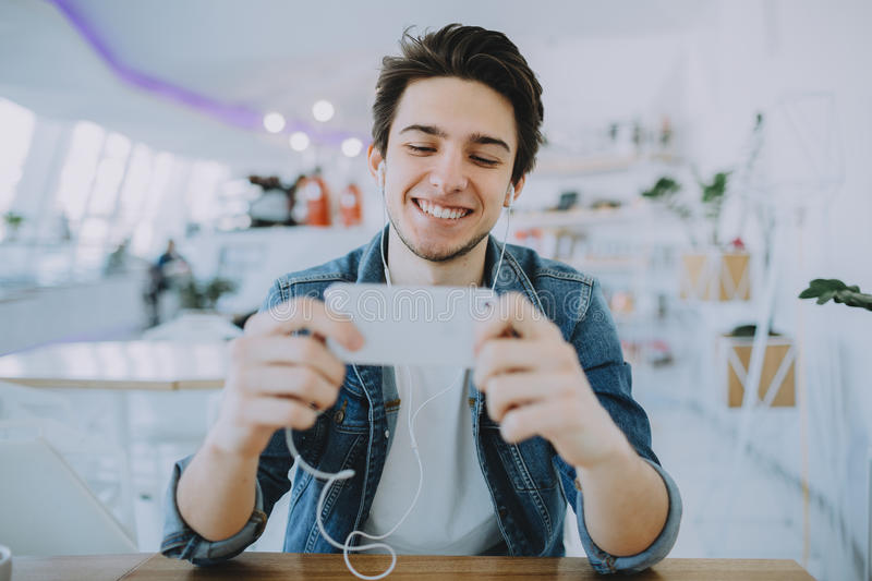 Attractive young man or freelance is sitting in cafe and using his mobile royalty free stock photo