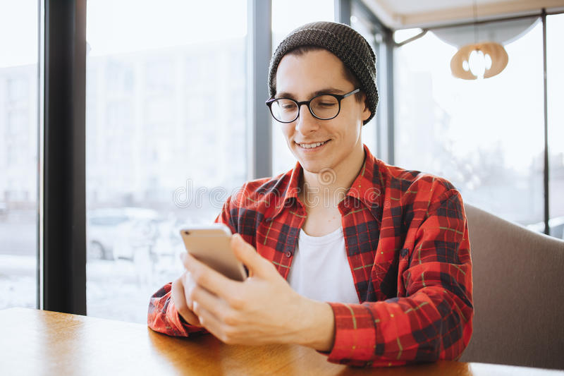 Attractive young man or freelancer is sitting in cafe during the coffee break royalty free stock images