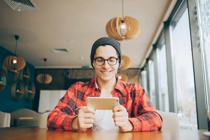 Attractive young man or freelancer is sitting in cafe stock images