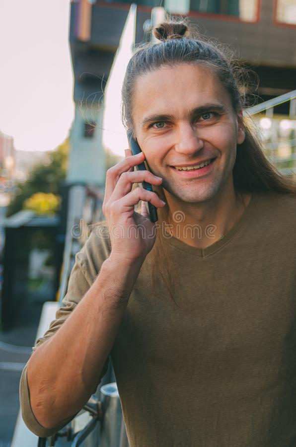 Attractive young man hipster talking on a smartphone while sitting on the steps of a glass business center. Urban fast life. Freelance worker stock image