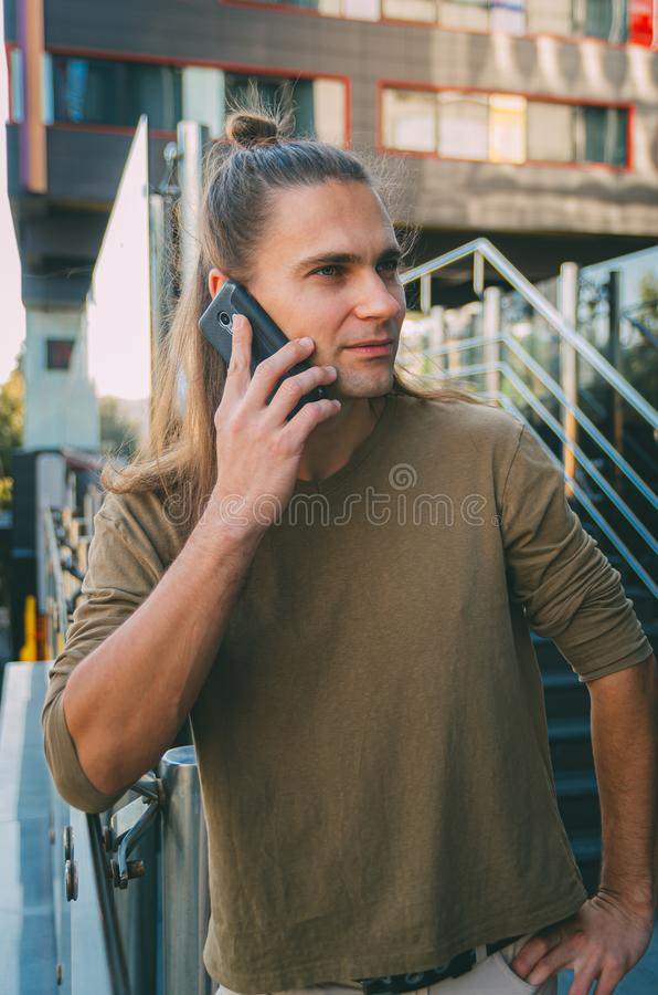 Attractive young man hipster talking on a smartphone while sitting on the steps of a glass business center. Urban fast life. Freelance worker royalty free stock image