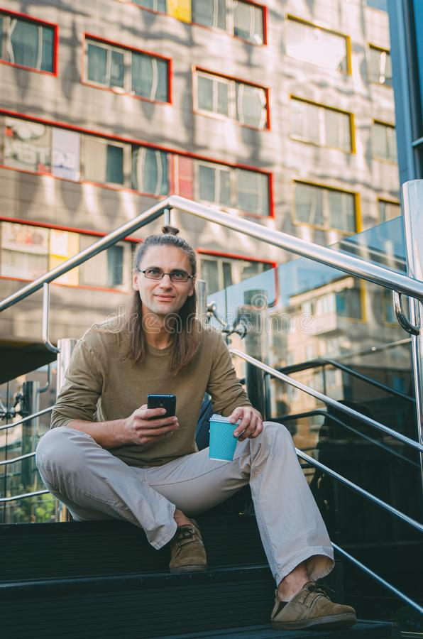 Attractive young man hipster writes a message on a smartphone while sitting on the steps of a glass business center. Urban fast. Life. Freelance worker royalty free stock photography