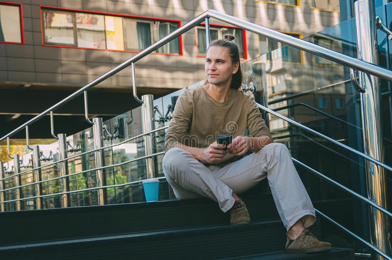 Attractive young man hipster writes a message on a smartphone while sitting on the steps of a glass business center. Urban fast. Life. Freelance worker stock images