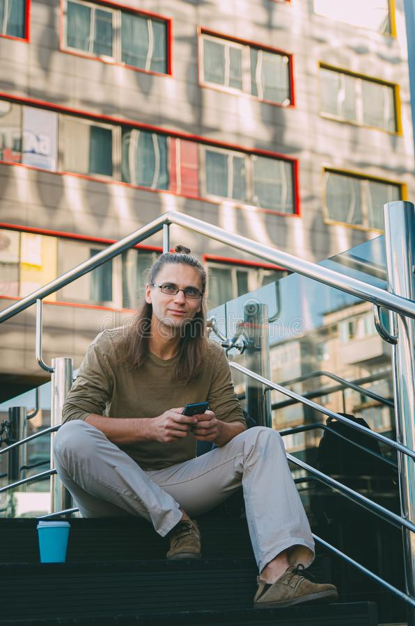 Attractive young man hipster writes a message on a smartphone while sitting on the steps of a glass business center. Urban fast. Life. Freelance worker stock image