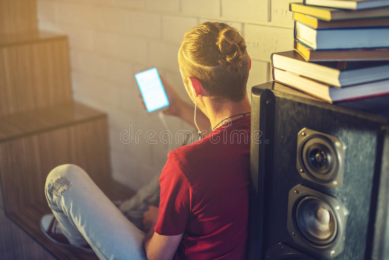 Attractive young man listening to the audio book in the headphones. Concept of technology education a positive lifestyle stock photo
