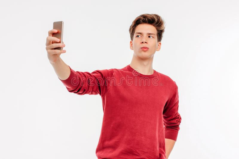 Attractive young man makes a selfie with smartphone on white bac royalty free stock photos