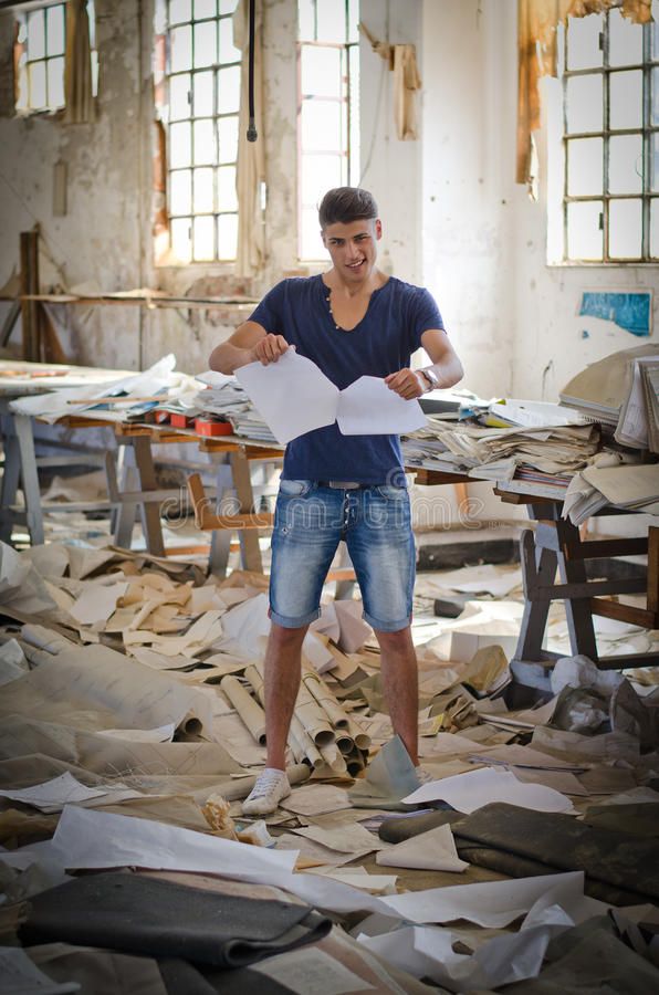 Attractive young man in messy office or working place stock images